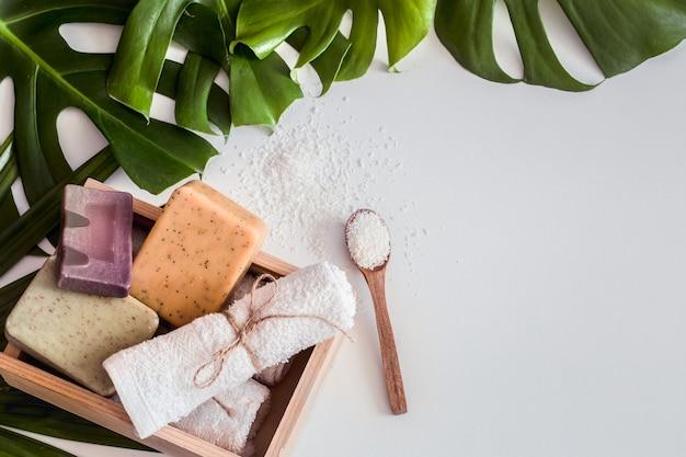 Skład spa z tropikalnymi liśćmi na białym tle.różne organiczne mydło, koncepcja pielęgnacji i urody, widok z góry
