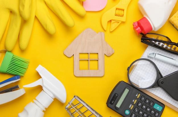 Skład sprzętów gospodarstwa domowego, narzędzi pracy, środków czystości i papeterii z domkiem pośrodku na żółto.