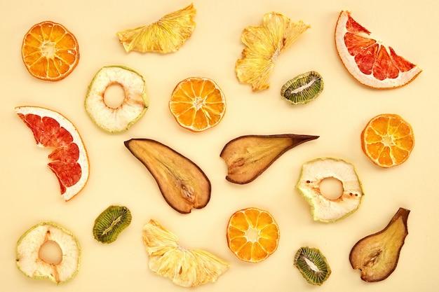 Skład suszonych owoców (kiwi, gruszka, mandarynka, pomarańcza, grejpfrut, jabłko) na kolorowym. widok z góry suszonych owoców