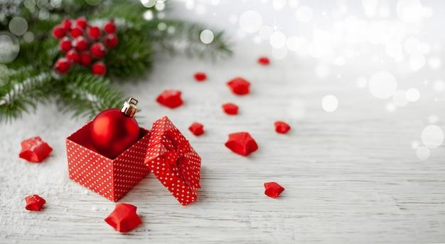 Skład świąt bożego narodzenia. christmas ball i prezent na jasnym tle z miejsca kopiowania tekstu. nieostrość.
