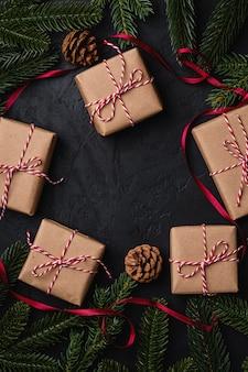 Skład świąt bożego narodzenia. czerwona wstążka, ozdoby i bombki oraz ekologiczne pudełka na prezenty. skopiuj miejsce