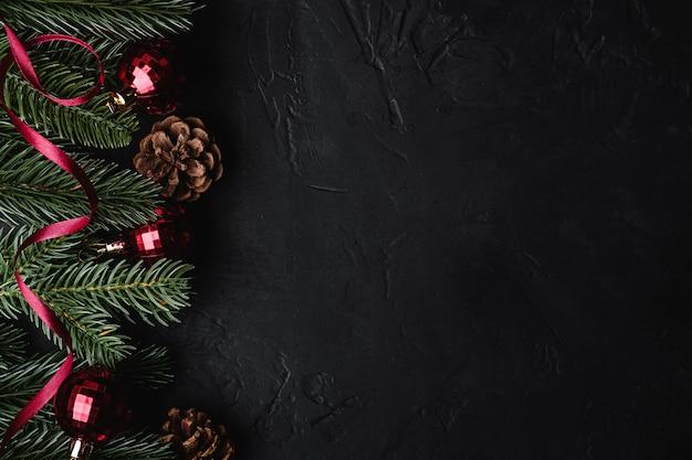 Skład świąt bożego narodzenia. czerwona wstążka, ozdoby i bombki, szyszki jodły i sosny. skopiuj miejsce