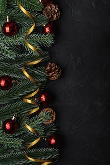 Skład świąt bożego narodzenia. złota wstążka, czerwony ornament i bombki, szyszki jodły i sosny. skopiuj miejsce