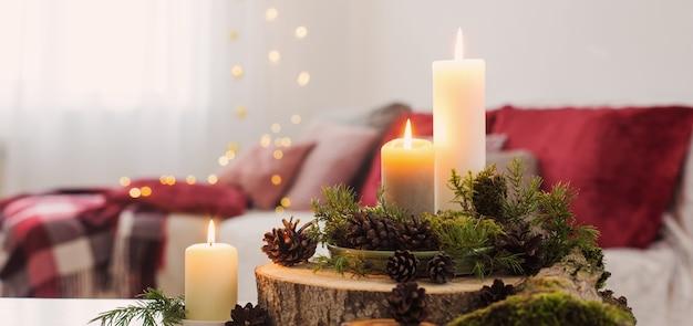 Skład świec na białym stole na tle kanapy w domu