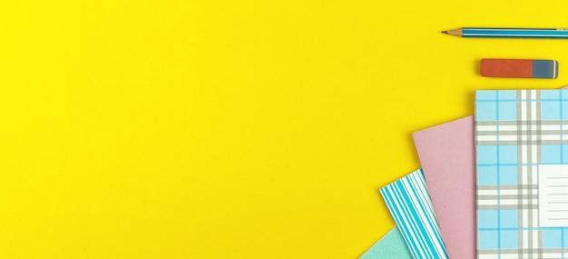 Skład szkolny i tło ze szkolnymi zeszytami zeszytowymi i ołówkiem z gumką na żółtym stole, widok z góry ze zdjęciem miejsca na kopię