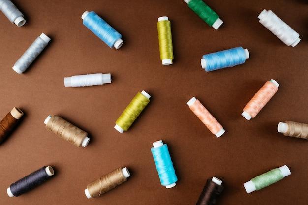 Skład szpulek nici układany na płasko, widok z góry. nici leżą na brązowym tle