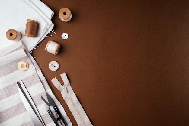 Skład szpulek z nicią i innymi akcesoriami do szycia na brązowym tle, płaskie płaskie, widok z góry
