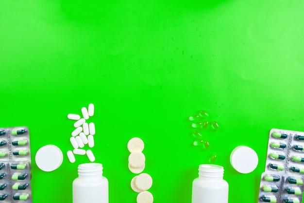 Skład tabletek, oleju rybnego, witamin na żółtej powierzchni