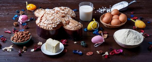 Skład typowego włoskiego deseru na uroczystości paqua zwanego colomba pasquale, z mąką, jajkami, lukrem, kandyzowanymi owocami i migdałami