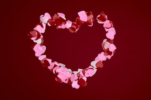 Skład walentynki z miejsca na kopię. rama wykonana z konfetti serca czerwone i różowe na pastelowym tle. zamknij się, widok z góry, miejsce na kopię