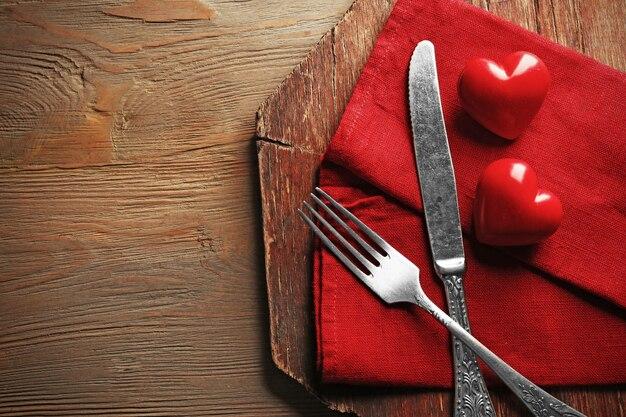 Skład widelec, nóż, serwetka i dekoracyjne serca na deska do krojenia, na tle drewniany stół