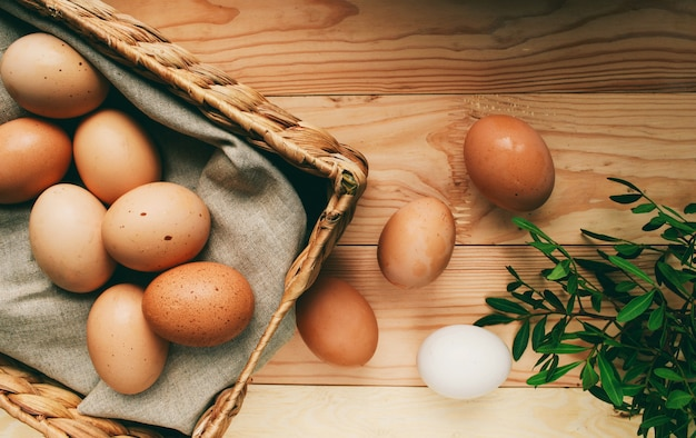 Skład wielkanocny pisanki leżą w skrzynce na jajka obok zielonych gałęzi na drewnianym jasnym tle zdjęcie wielkanocne zdjęcie z góry