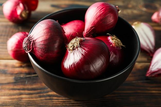 Skład z czerwoną cebulą na drewnianym stole