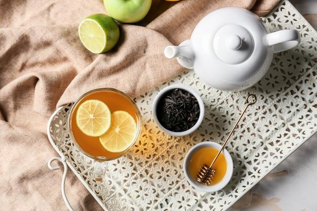 Skład z filiżanką gorącej zdrowej herbaty na jasnym tle