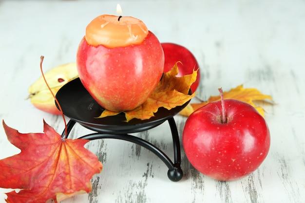 Skład z jabłkami i świeczką na drewnianym
