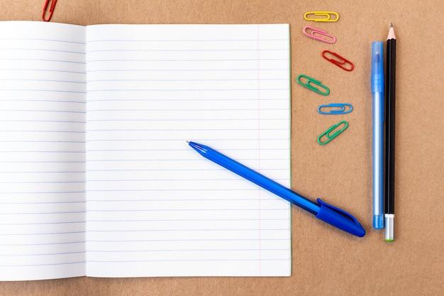 Skład z kolorowy ołówek pusta strona notatnik, marker i długopis z miejsca na kopię. powrót do koncepcji szkoły na tle kartonu rzemiosła