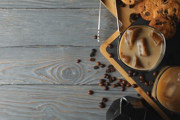 Skład z lodową kawą i ciastkami na drewnianym tle