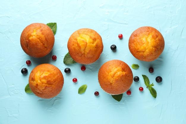 Skład z muffins i jagodami na błękitnym tle, odgórny widok