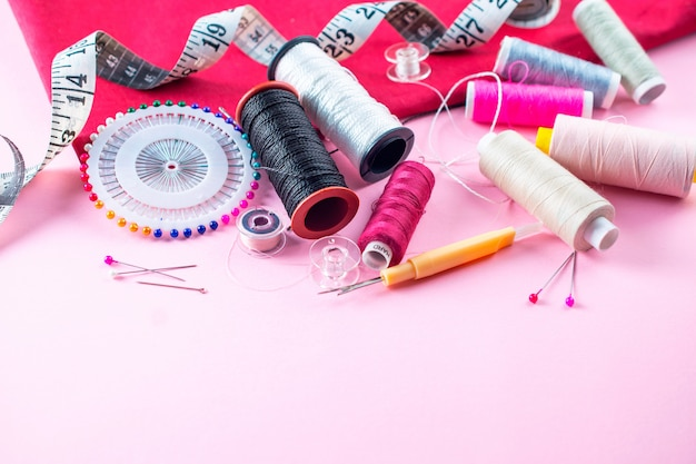 Skład z niciami i szwalnymi akcesoriami na różowym tle