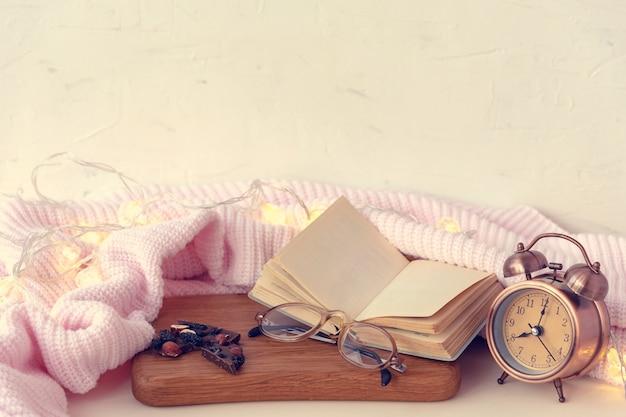 Skład z otwartą pustą książkę, okulary i retro budzik