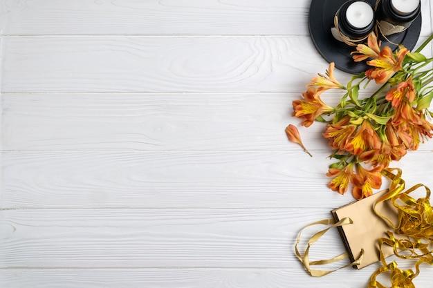 Skład z prezent torby kwiatami i świeczki prezenta tłem z copyspace. widok płaski z góry