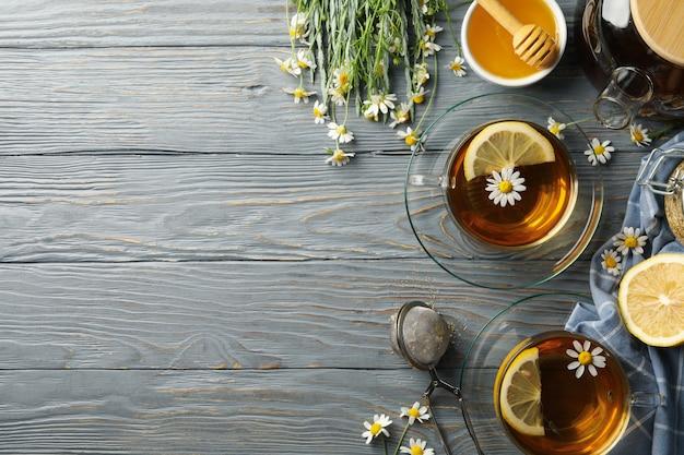 Skład z rumianku herbatą na szarym drewnianym tle
