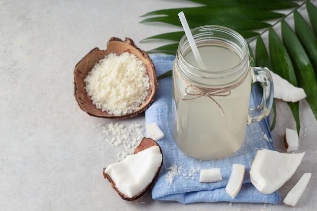 Skład z słoikiem wody kokosowej na szarym stole, miejsce na tekst