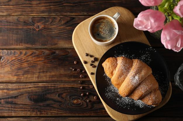 Skład z smakowitym croissant na drewnianym tle, odgórny widok