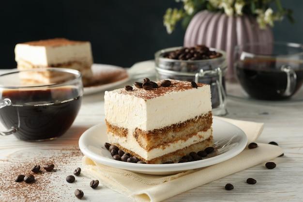 Skład z smakowitym tiramisu na białym drewnianym tle. pyszny deser