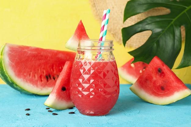 Skład z sokiem z arbuza na niebieskim stole. letni owoc
