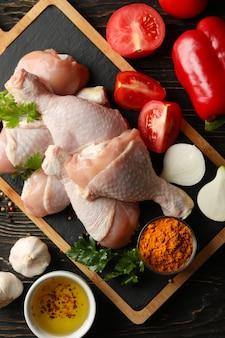 Skład z surowym kurczaka mięsem na drewnianej przestrzeni, odgórny widok