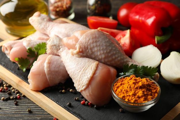 Skład z surowym kurczaka mięsem na drewnianej przestrzeni, zamyka up