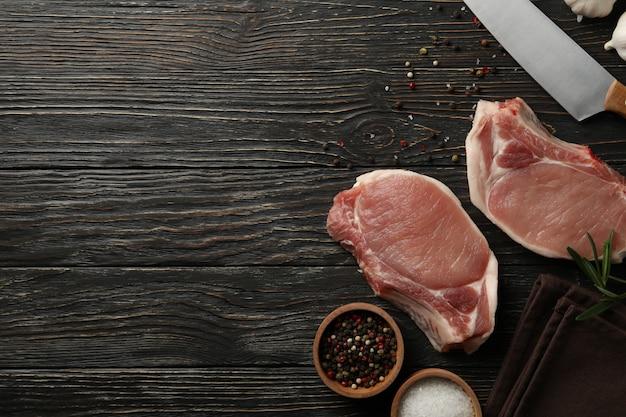 Skład z surowym mięsem na stek i składnikami na drewnianym stole