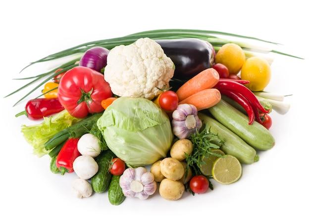 Skład z surowymi warzywami na białym tle.