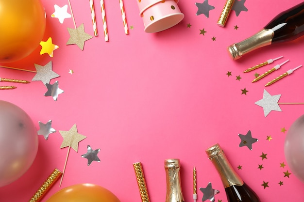 Skład z szampanem i urodzinowymi akcesoriami na różowym tle, przestrzeń dla teksta