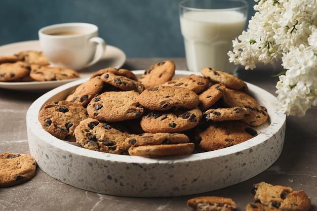 Skład z tacą ciasteczek z kawałkami czekolady na jasnobrązowym stole.