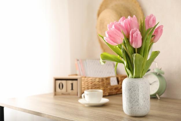 Skład z tulipanami w wazie na drewnianym tle, przestrzeń dla teksta