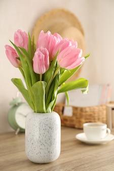 Skład z tulipanami w wazie na drewnianym tle, zamyka up