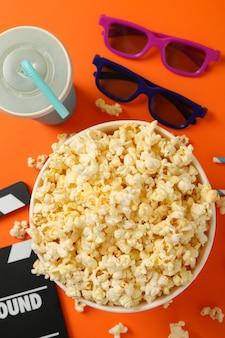 Skład z wiadrem popcornu na pomarańczowo. jedzenie do oglądania kina