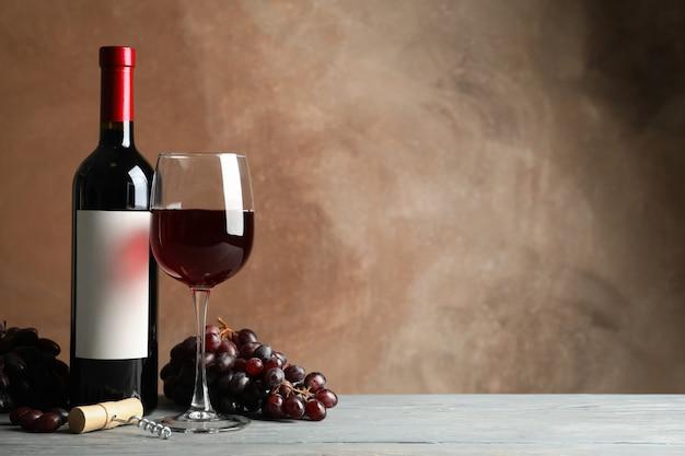 Skład z wina, korka i winogron na brązowym tle