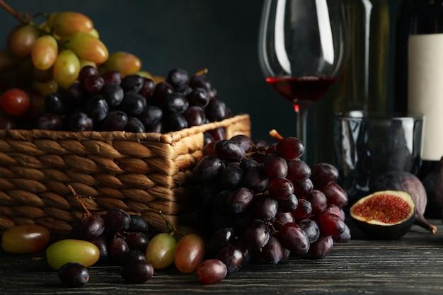 Skład z winogronem, winem i figą na drewnianym stole