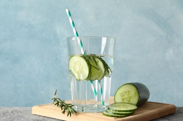 Skład ze szklanką ogórka wody na szary stół