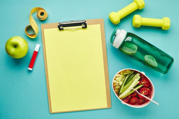 Składana tabletka na papier, butelkę wody, hantle, miarkę i pudełko na drugie śniadanie ze zdrową sałatką warzywną. pojęcie planowania ćwiczeń i prawidłowego odżywiania