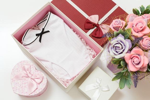Składane bawełniane figi w pudełeczko ze sztucznymi kwiatami na białym tle zestaw bielizny damskiej.