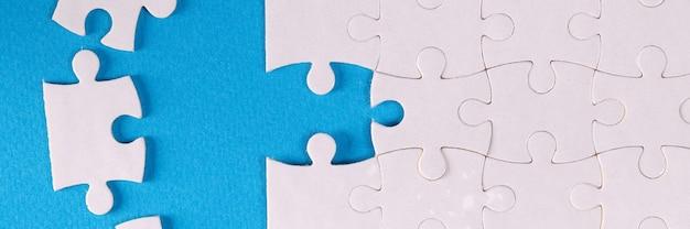 Składane białe puzzle na niebieskim tle
