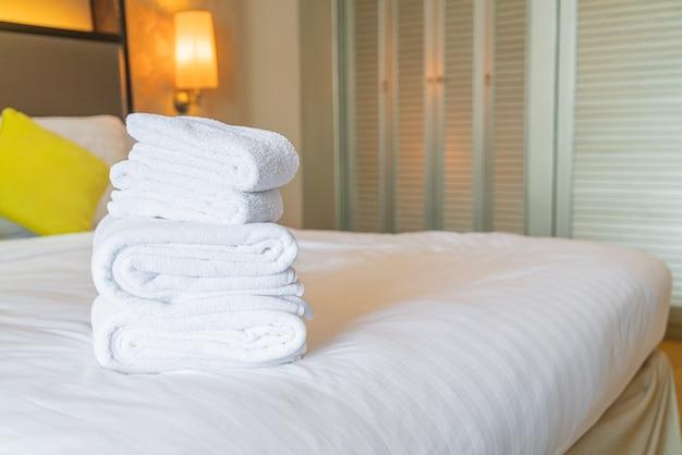 Składane białe ręczniki na łóżku
