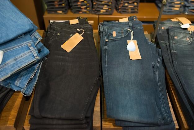 Składane dżinsy męskie na półce w sklepie odzieżowym, zbliżenie