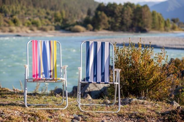 Składane krzesła na brzegu górskiej rzeki w miły, ciepły dzień. spokojne i ciche miejsce na relaks i refleksję. sprzęt i wypoczynek turysty.