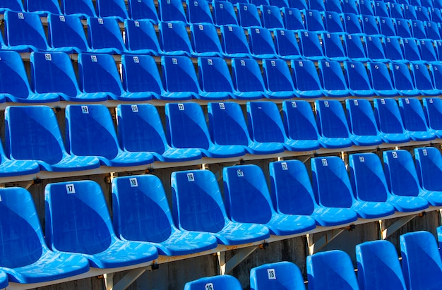 Składane niebieskie plastikowe krzesła na tymczasowej trybunie,