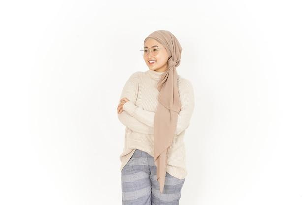 Składane ramiona i uśmiech pięknej azjatyckiej kobiety noszącej hidżab na białym tle